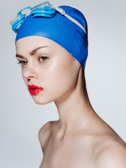 Kobieta z odkrytymi ramionami okulary pływackie czerwone usta sport fitness