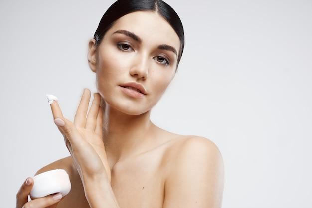 Kobieta z odkrytymi ramionami słoik krem do pielęgnacji skóry nawilżający
