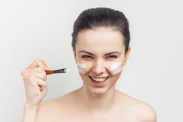 Kobieta z odkrytymi ramionami z pędzelkiem w rękach stosowania makijażu