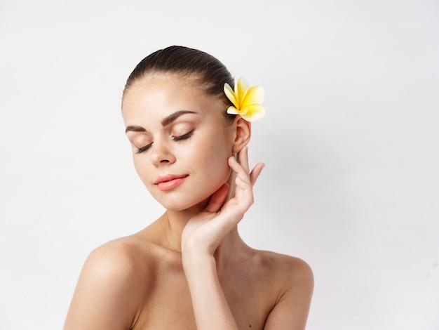 Kobieta z odkrytymi ramionami, zamkniętymi oczami, żółty kwiat we włosach