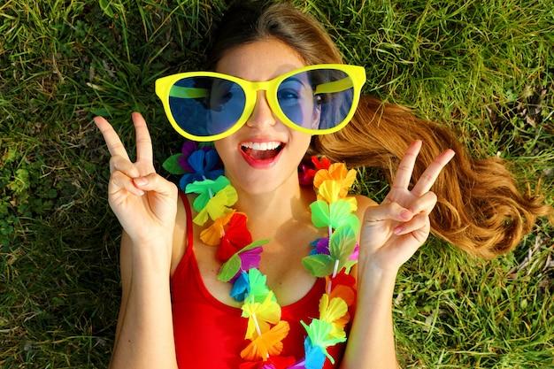 Kobieta z ogromnymi okularami i girlandą festiwalu
