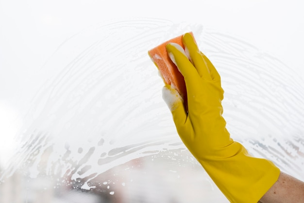 Kobieta z oknem do czyszczenia rękawic gumowych