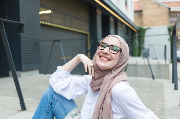 Kobieta z okularami i hidżabu uśmiechnięty