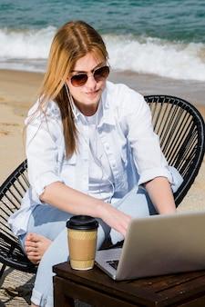 Kobieta z okularami przeciwsłonecznymi i laptopem pracuje przy plażą