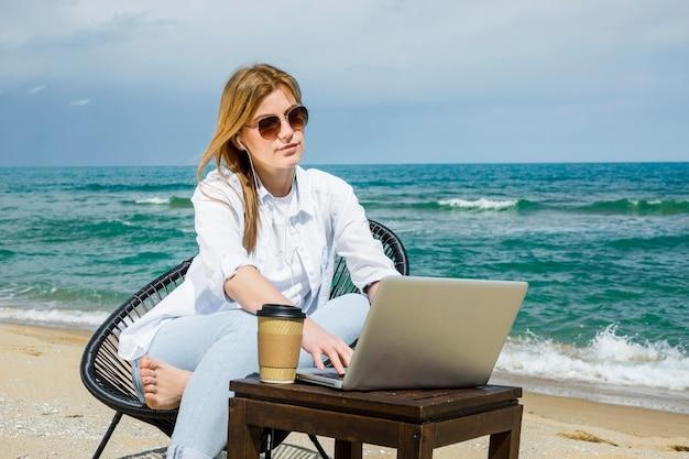 Kobieta z okularami przeciwsłonecznymi pracuje przy plażą