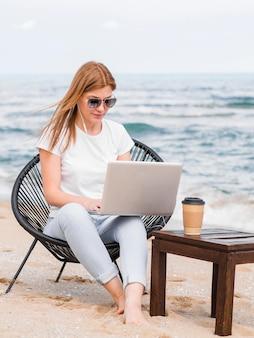 Kobieta z okularami przeciwsłonecznymi w plażowym krześle pracuje na laptopie