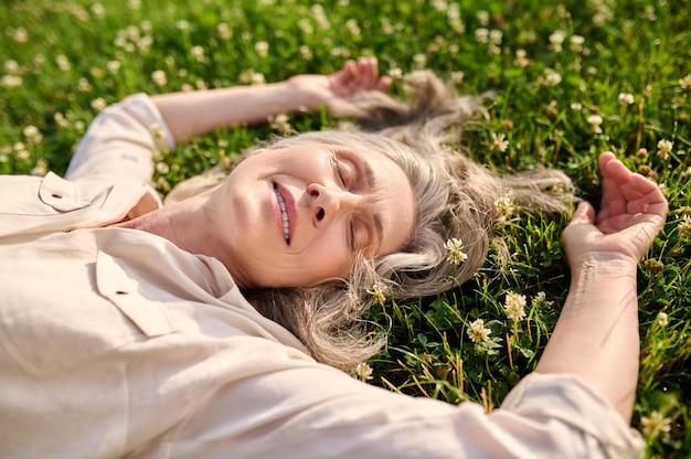 Kobieta z opadającymi powiekami leżąca na trawie