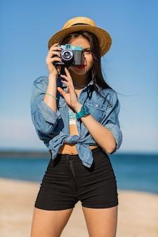 Kobieta z opalonym ciałem, pełnymi czerwonymi ustami i długimi nogami pozuje na tropikalnej słonecznej plaży. nosi krótki top, szorty i słomkowy kapelusz.