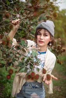 Kobieta z organicznych owoców rambutanu w sadzie
