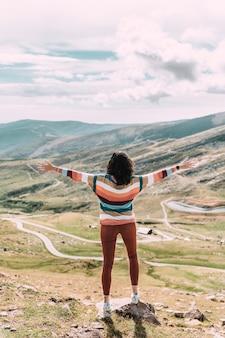 Kobieta z otwartymi ramionami przeciw niebu i górskiej dolinie.