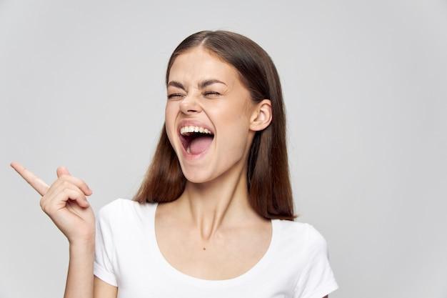 Kobieta z otwartymi ustami i zamkniętymi oczami pokazuje palcem z boku na białym tle