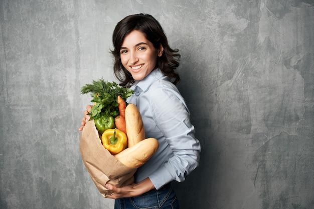 Kobieta z paczką artykułów spożywczych kupuje warzywa