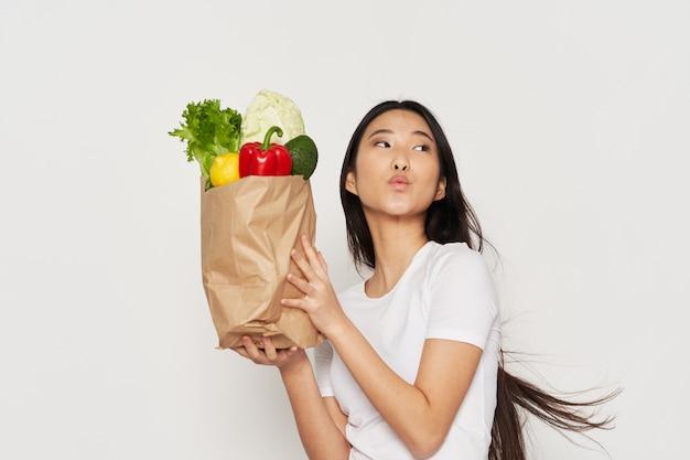 Kobieta z pakietem artykułów spożywczych gospodyni zakupy wegetariańskie zdrowej żywności