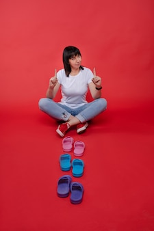 Kobieta z palcami i kolorowe japonki. loor z palcami wskazującymi w górę i kolorowymi jasnymi klapkami przed nią ..