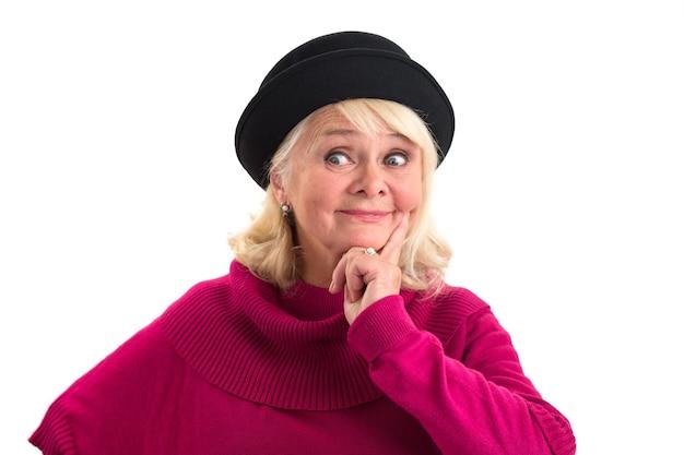 Kobieta z palcem na policzku zamyślona starsza pani na białym tle wyobraża sobie przyszłość