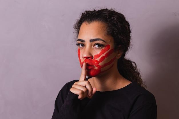 Kobieta z palcem na ustach robi znak ciszy. przemoc domowa