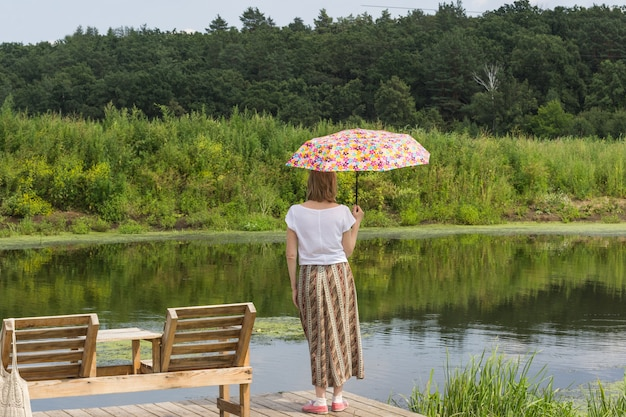 Kobieta z parasolem stoi na brzegu rzeki. las po drugiej stronie