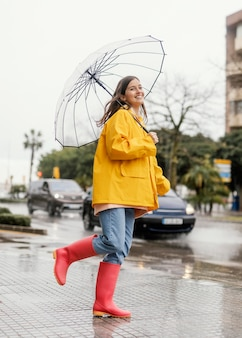 Kobieta z parasolem stojąc w deszczu długi widok
