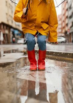 Kobieta z parasolem stojąc w deszczu