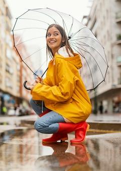 Kobieta z parasolem stojąc w widoku z boku deszczu