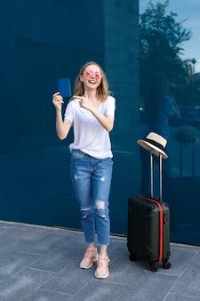 Kobieta z paszportem i bagażem w okularach na wakacjach