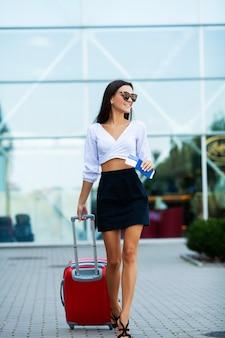 Kobieta z paszportem i czerwoną walizką w pobliżu lotniska wybiera się w podróż