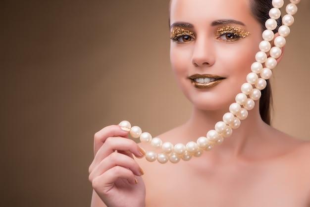 Kobieta z perełkową kolią odizolowywającą na bielu