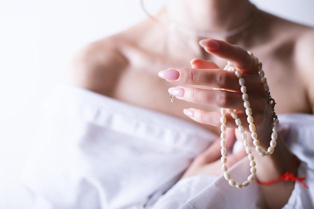 Kobieta z perłą diamentową kolią w ręku