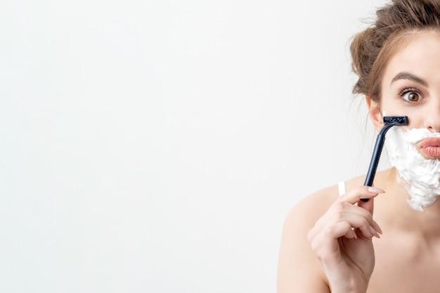 Kobieta z pianką do golenia na twarzy