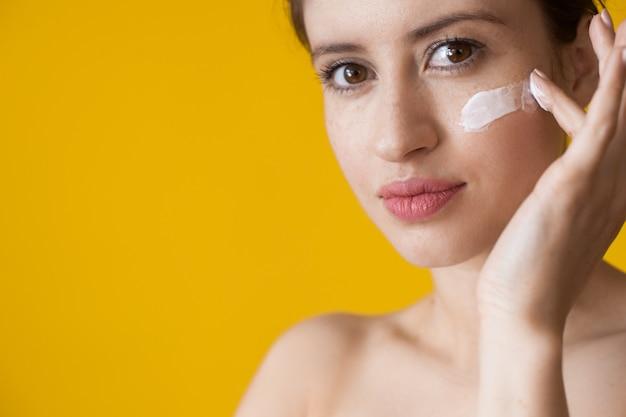 Kobieta z piegami nakłada krem na twarz przeciw starzeniu
