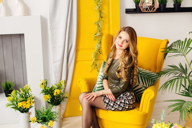 Kobieta z piękną fryzurą siedzi na żółtym fotelu przy kominku i żółtych drzwiach z zasłoną i wokół kwiatów w wazonach