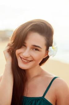 Kobieta z piękna twarz dotyka skóry. piękna uśmiechnięta dziewczyna model na plaży. młoda uśmiechnięta kobieta portret na zewnątrz.