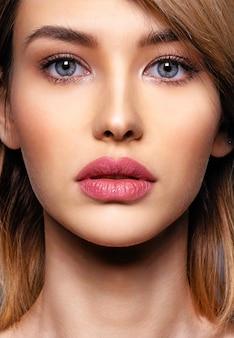 Kobieta z piękną twarzą i czystą skórą. seksowna blondynka. atrakcyjny blond model z niebieskimi oczami. modelka z smokey makijaż. zbliżenie portret ładnej kobiety. kreatywna krótka fryzura.