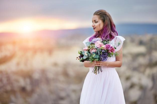 Kobieta z pięknym bukietem kwiatów w jej ręce stoi