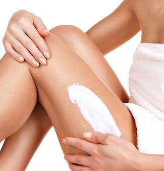 Kobieta z pięknym ciałem za pomocą kremu na nogę na białym