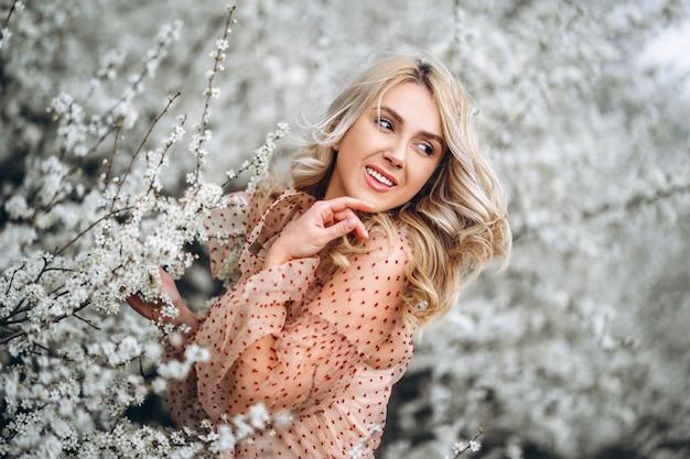 Kobieta z pięknym uśmiechem, kręcone blond włosy w czerwonej sukience zabawy w kwitnący ogród