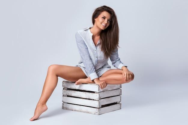 Kobieta z pięknymi nogami siedzi na drewnianym pudełku