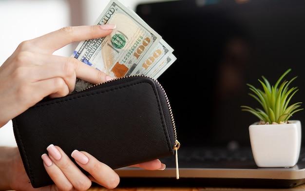 Kobieta z pieniądze przy miejscem pracy. pomysł na biznes