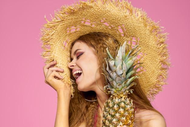 Kobieta z pistoletem w rękach słomkowego kapelusza jasny makijaż egzotyczne owoce lato różowe tło
