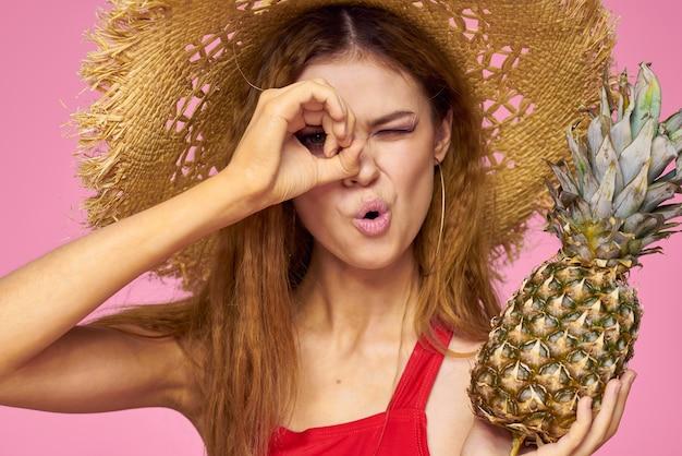Kobieta z pistoletem w rękach słomkowego kapelusza jasny makijaż egzotyczne owoce lato różowy