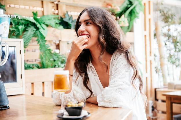 Kobieta z piwa jedzenia oliwek