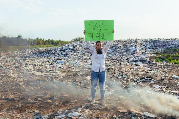 Kobieta z plakatem ratuje planetę, pikietuje skażone śmieciami środowisko, płonący ogień i czarny dym