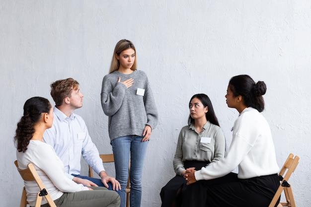 Kobieta z plakietką mówi podczas sesji terapii grupowej