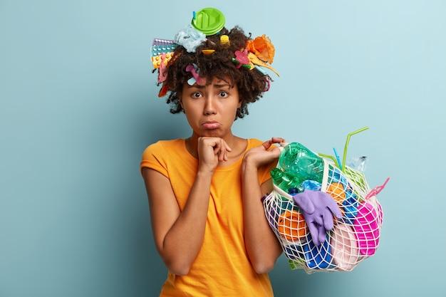 Kobieta z plastikowymi odpadami w siatkowej torbie