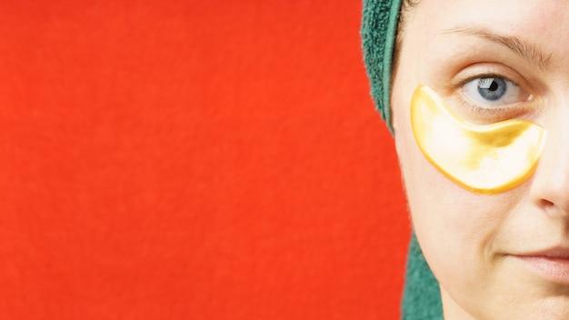 Kobieta z plastrami pod oczami koncepcja pielęgnacji skóry nawilżająca maska przeciw starzeniu się pod oczy złote plastry hydrożelowe