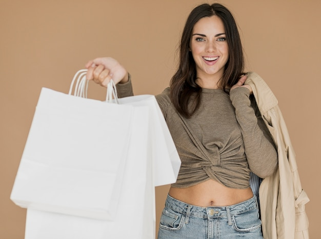 Kobieta z płaszczem na ramieniu i białe torby na zakupy
