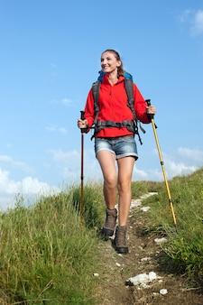 Kobieta z plecakiem i kijkami trekkingowymi