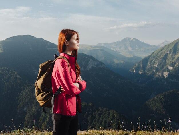 Kobieta z plecakiem podróżuje turystyka górska wolność