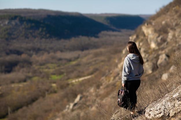 Kobieta z plecakiem stojącym na skale i patrzy na piękny krajobraz