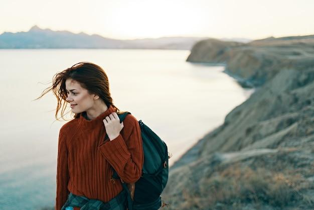 Kobieta z plecakiem w czerwonym swetrze w górach
